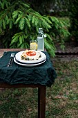 A slice of spinach lasagne served with lemonade on a table outdoors