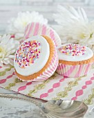 Cupcakes decorated with icing and colourful sugar sprinkles