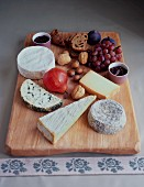 A cheese board with fruit, nuts and bread