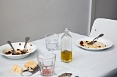 Empty pasta plates, a bottle of olive oil, and blocks of Parmesan on a restaurant table