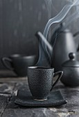 Steaming tea in a black cup