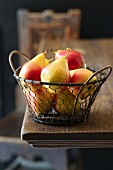 Yellow and red pears in a wire basket on a wooden table