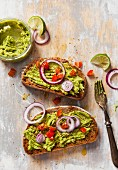 Two slices of avocado on toasted bread garnished with fresh diced tomato and sliced red onion