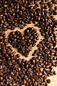 Coffee beans in the shape of a heart on a cork background