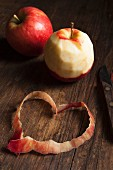 Two whole apples, one peeled, and a heart made out of the peelings