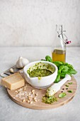 Basil pesto in mortar surrounded by the ingredients