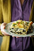 A person holding a plate of spinach lasagne