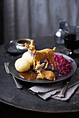 Two toy deer on a plate with red cabbage, dumplings and gravy