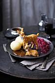 Zwei Spielzeug-Rehe auf Teller mit Rotkohl, Klössen und Bratensauce