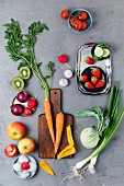 An arrangement of spring onions, garlic, apples, tomatoes, peppers, carrots, kiwi, radishes, strawberries and kohlrabi