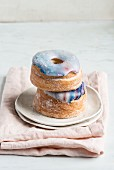 Two galaxy croissant doughnuts with marble glaze on top of each other