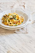 Fresh homamade tagliatelle with yellow and green courgette, bacon and goat cheese
