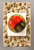 Feta, Tomaten, Gurke und Olive auf Kürbiskernknäckebrot