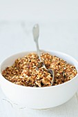 Coarsely ground hazelnut brittle in a white porcelain bowl