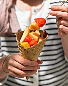 An ice cream cone filled with chocolate and fruit salad for a summer picnic