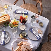 A table laid with a poultry pie, carrots, peppers, chicory and white bread