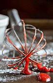 A whisk covered in Strawberry sauce