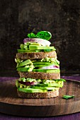 A stack of toasted avocado sandwiches