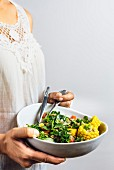 A woman wearing a white lace top holding a bowl of lentil salad in her hands