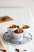 Biskuit-Muffins in Pappförmchen auf Kuchengitter