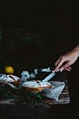 Frauenhand schneidet Mini-Biskuitkuchen