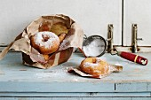 Homemade donuts with sugar powder from paper bag served with vintage sieve on blue wooden table