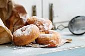 Hausgemachte Donuts mit Puderzucker in Papiertüte auf Holztisch