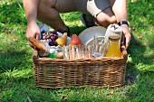 Junger Mann trägt Picknickkorb mit Getränken, Obst und Sandwiches