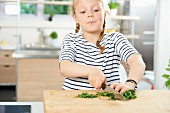 A girl chopping fresh parsley