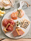 A cheese plate with raw ham and butter balls for brunch