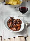 Beef bourguignon with a glass of red wine and ribbon noodles