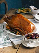 Roast goose with red cabbage and chestnuts on a rustic table