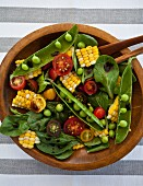 A spinach salad with corn, heirloom tomatoes and green peas, with balsamic vinegar drizzled on top
