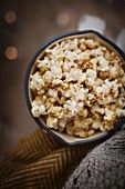 Vanilla and cinnamon pop corn in an annamel pan with blankets against a dark background with fairy lights