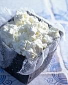 Fresh cheese on gauze cloth in a container