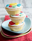 A stack of cupcakes with colourful fondant dots