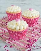 Cupcakes mit Cremetupfen und rosa Herzen