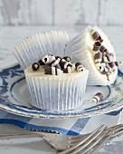 Cupcakes with buttercream and black and white chocolate rolls