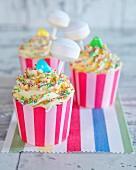 Cupcakes mit bunten Zuckerperlen und Lolli