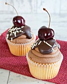 Cupcakes with chocolate icing and a cherry