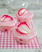 Cupcakes with pink fondant icing and a rose petal