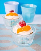 Cupcakes with cream frosting, a raspberry and apricot on the top