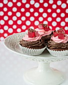 A cupcake with chocolate and raspberry cream and jelly cubes