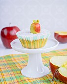A cupcake with fondant icing and a marzipan apple