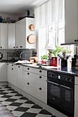 weiße Küche mit Kassettenfronten und Schachbrettmusterboden