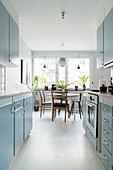 Retro-Küche mit hellblauen Fronten und Esstisch vor dem Fenster