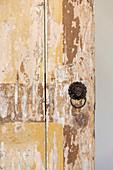 Detail einer Tür mit abgeblätterter Farbe und Löwenkopfgriff