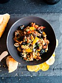 Eggplant caponata with walnuts in dark bowl