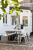 Esstisch mit Stühlen und Hockern auf der Terrasse