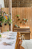 Flower arrangements suspended over set dining table in converted barn
